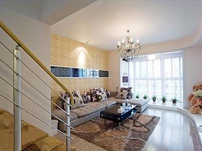 装修选用白杉木强化地板,客厅沙发区,米黄色的壁纸铺成温馨的沙发背景
