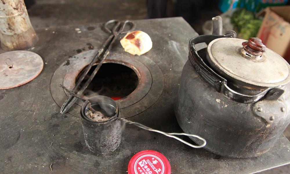 4烤茶时,先把小瓦罐放于火上烤热,再放入茶叶,然后边烘烤边轻轻抖动,直至茶叶颜色变黄,发出焦香气味时,再将其倒入杯内,用沸水冲泡饮用。