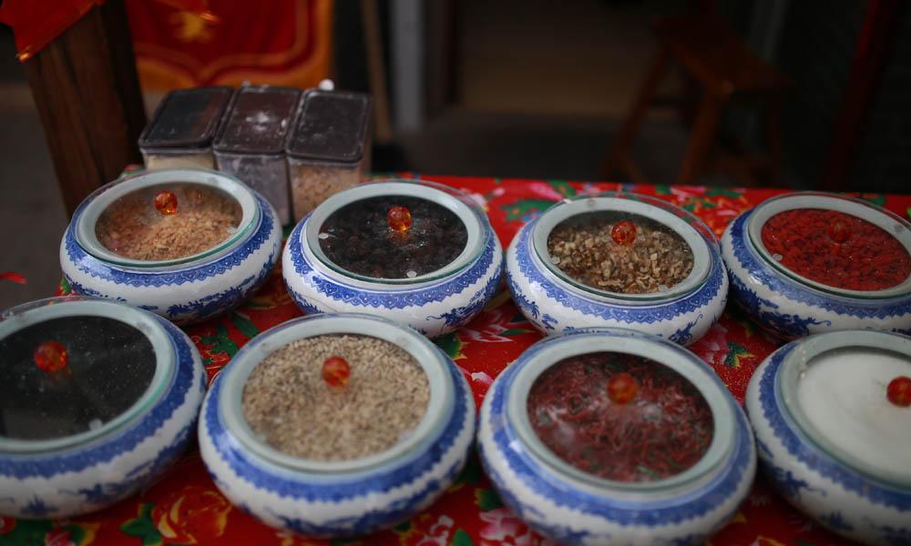 2.桌上摆着八种佐料,和其他的配料,配料多为青红丝,主要有萝卜、芥菜、橘皮、冬瓜、西瓜皮等原料。