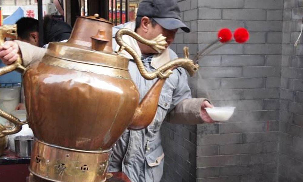 5.然后从铜壶里冲入滚水搅成糊状茶汤,大铜壶沸水要冲开,大铜壶俗称茶汤壶,是茶汤业的幌子。