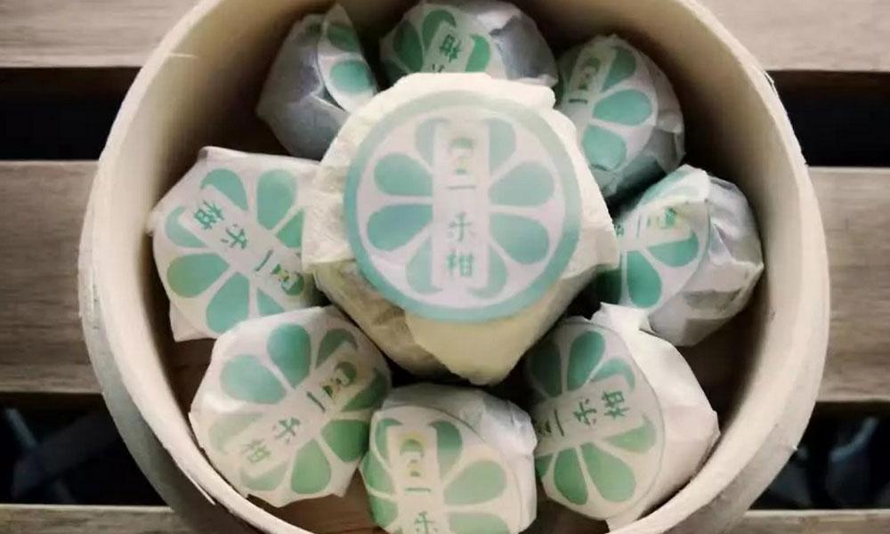 5.烘焙好的小青柑用棉纸和贴纸包裹起来,现在就基本上和卖的小青柑一样了;可以装进小蒸笼,送朋友,大方好看,平时保存建议放在密封的罐子里,这个越存放得久,越香。